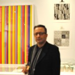 Graphic Designer Gabor Palotai in front of his graphic work